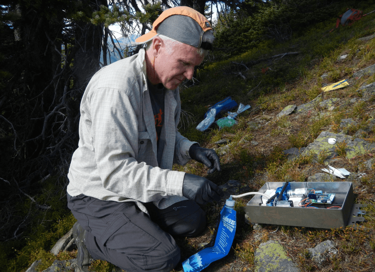 Robert Long prepares an automated scent dispenser meant to attract wolverines. The dispenser, which will be hung high in a tree above the snow line, will assist researchers in their effort to study wolverines in the winter when the Cascades are difficult to access. Photo by Paula MacKay.