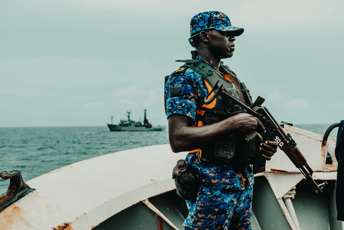 A Gambian navy sailor stands guard aboard an arrested trawler, with Sea Shepherd's Sam Simon in the background (Image © Sea Shepherd Global)