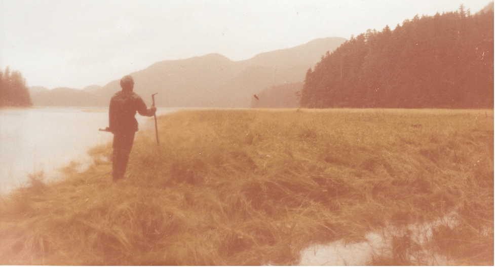 The author, in rain gear and hip waders, observing a bald eagle take flight from a misty tidal meadow on Ford Arm, Chichagof Island, Alaska, 1982
