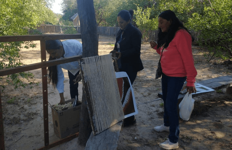 Local weavers learn from each other in the plaza of La Armonia
